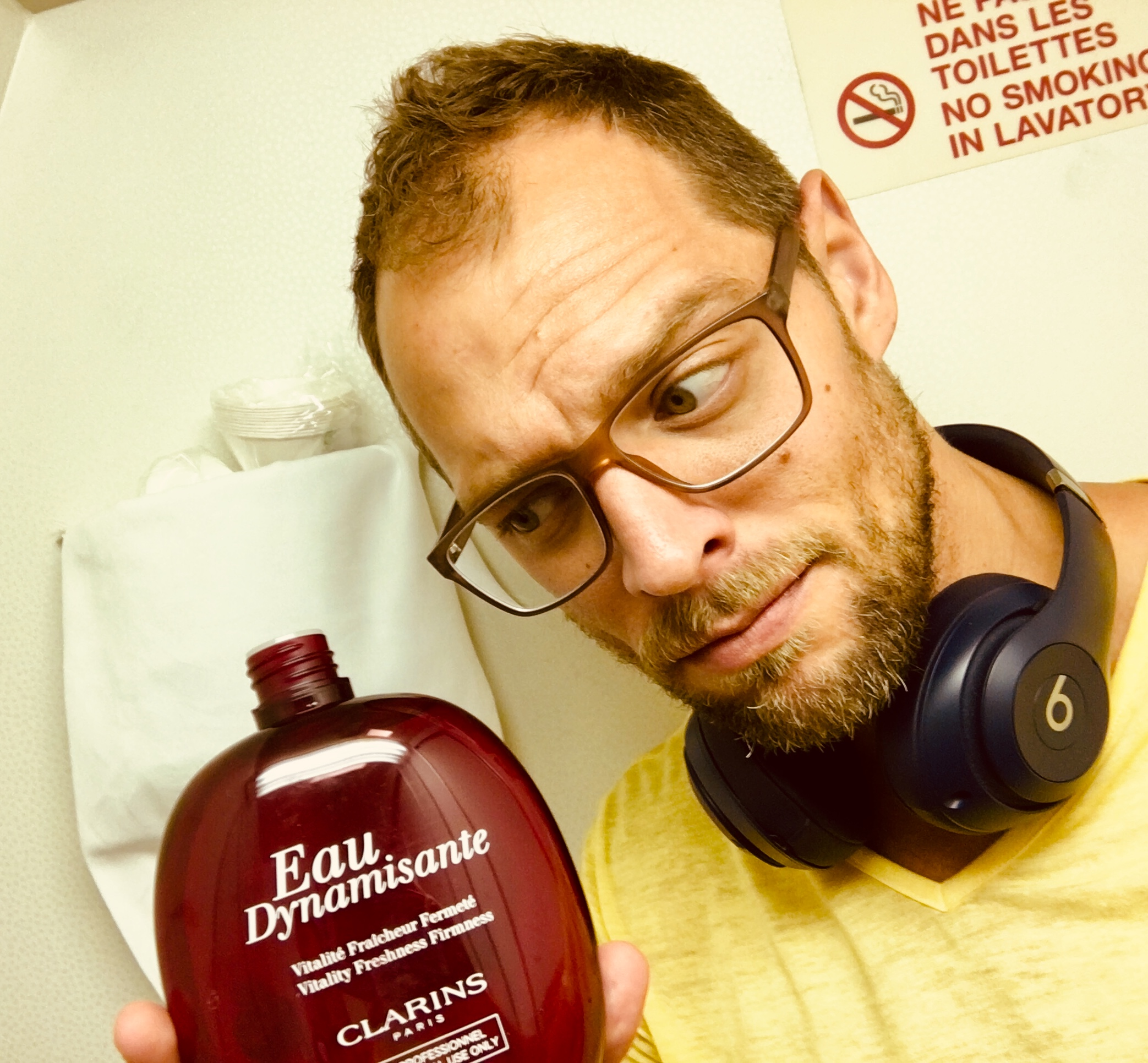 JSB holding bottle of Eau Dynamisante (air freshener?) in Air France lavatory
